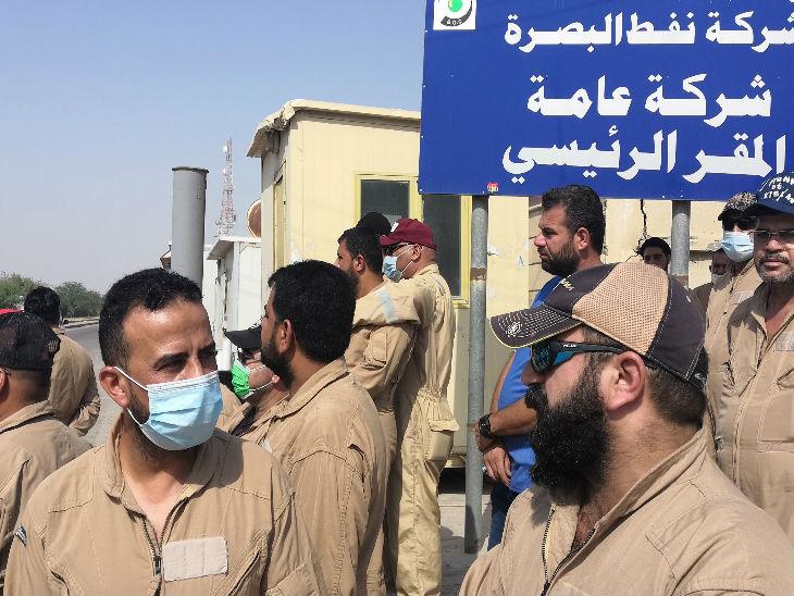 इराक के बसरा में लॉकडाउन के बीच नौकरी से हटाने पर प्रदर्शन करने के लिए एकजुट हुए एक ब्रिटिश तेल कंपनी के कर्मचारी।