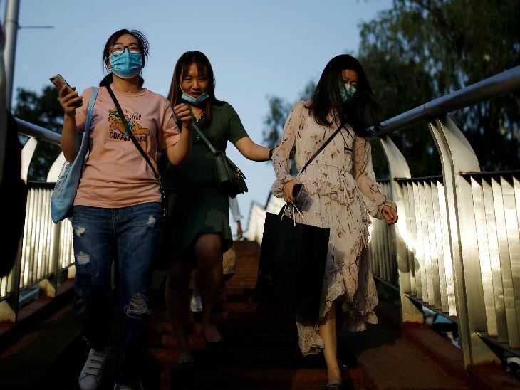 चीन में लॉकडाउन हटाने के बावजूद लोग सावधानी बरत रहे हैं। शनिवार को बीजिंग में मास्क लगाकर जाती लड़कियां।