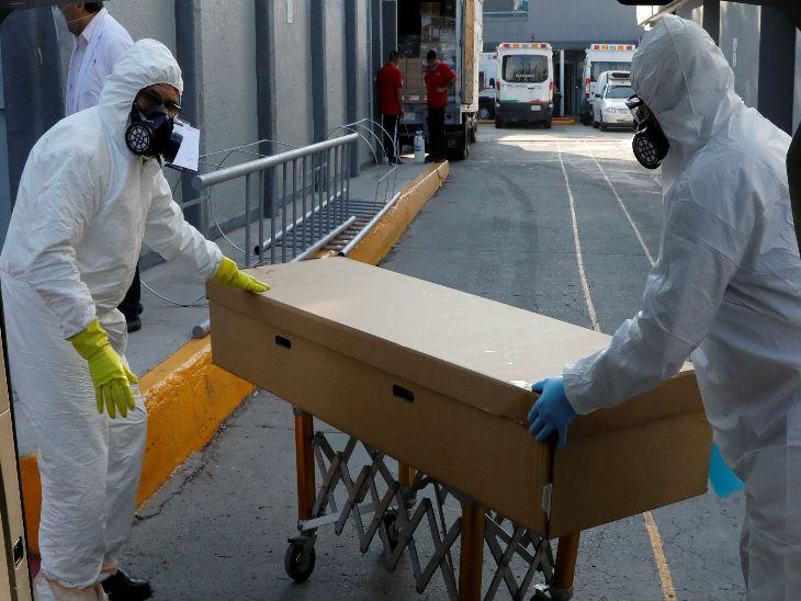 न्यू मैक्सिको सिटी में शनिवार को ताबूत में रखे एक शव को दफनाने ले जाते स्थानीय कर्मचारी।