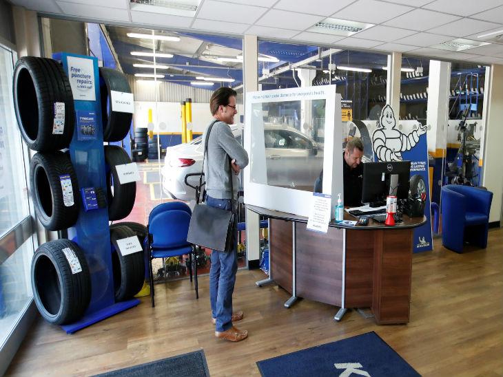 ब्रिटेन के ब्लेश्ले में प्रोटेक्टिव स्क्रीन के सामने खड़े होकर दुकानदार से बात करता एक व्यक्ति