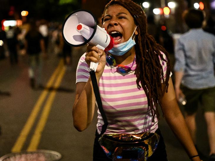 यह फोटो न्यूयॉर्क शहर की है। यहां प्रदर्शन के दौरान एक लड़की मेगाफोन से रंगभेद के खिलाफ आवाज उठाती हुई।