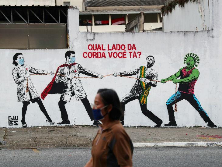 यह फोटो साओ पाउलो की है। इसमें ब्राजील के राष्ट्रपति जायर बोल्सोनारो और स्वास्थ्यकर्मियों को एक-दूसरे के खिलाफ रस्सी खींचते दिखाया गया है। साथ ही दीवार पर लिखा है- आप किस साइड हैं?