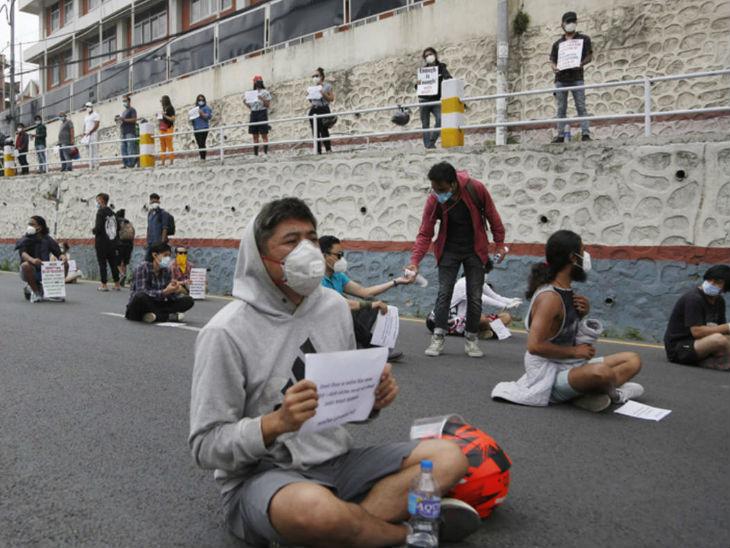 नेपाल की राजधानी काठमांडू में युवा पर्चे और तख्ती के साथ सड़क पर बैठकर सरकार के खिलाफ प्रदर्शन करते हुए। यहां बीते चार दिनों से लगातार प्रदर्शन हो रहे हैं।