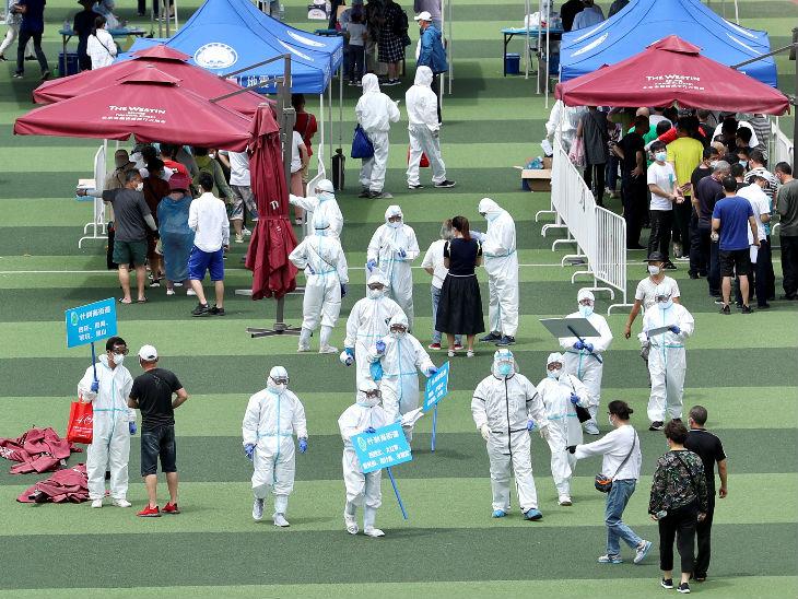 बीजिंग के एक स्टेडियम में कोरोना की जांच के लिए लोगों का सैंपल लेते स्वास्थ्यकर्मी। यहां मंगलवार को 31 नए मामले सामने आए हैं।