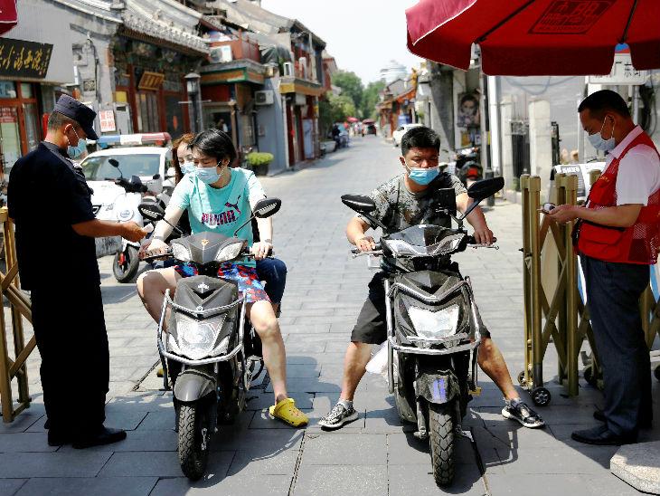 बीजिंग के एक रिहायशी एरिया में जाने से पहले लोगों का तापमान चेक करते सुरक्षागार्ड।