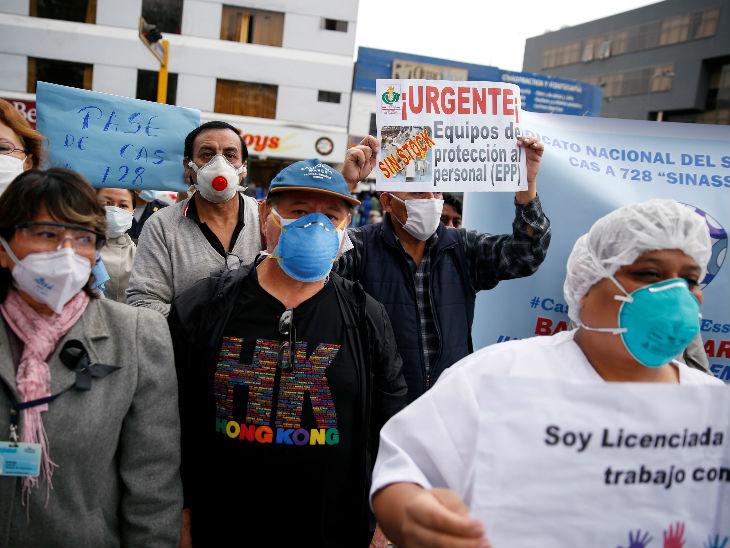 पेरू की राजधानी लीमा में एक अस्पताल के बाहर इक्विपमेंट की कमी को लेकर प्रदर्शन करते स्वास्थ्यकर्मी।