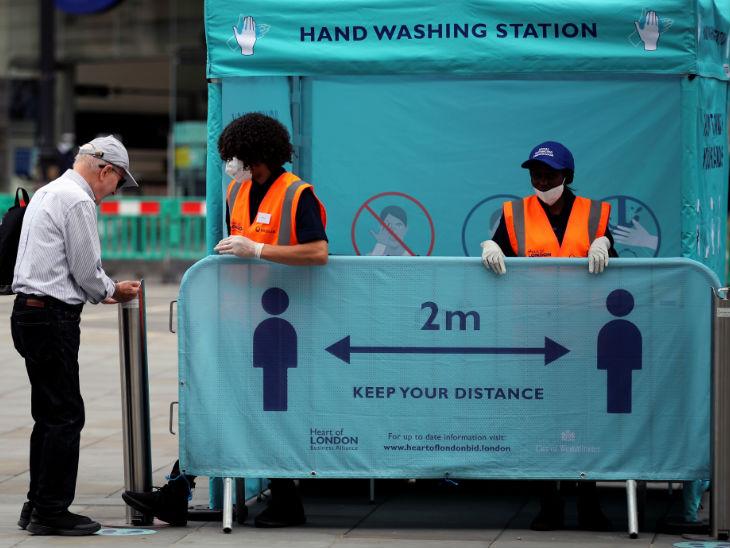 लंदन में महामारी के बीच एक व्यक्ति पिकाडिली सर्कस पर हैंड सेनिटाइजिंग स्टेशन पर हाथ साफ करता हुआ। यहां लोगों को एक-दूसरे के बीच 2 मीटर दूरी बनाए रखने का संदेश दिया जा रहा है।