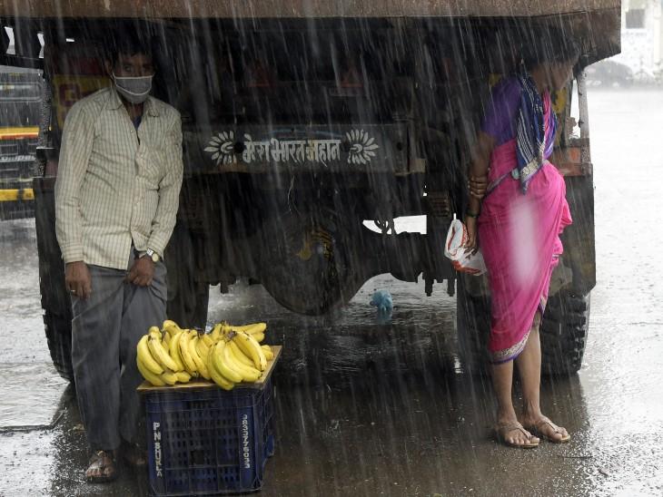 मुंबई में मानसून की दस्तक के बाद से रुक-रुक कर बारिश हो रही है। बरसात के बीच फल बेचता एक फेरीवाला।