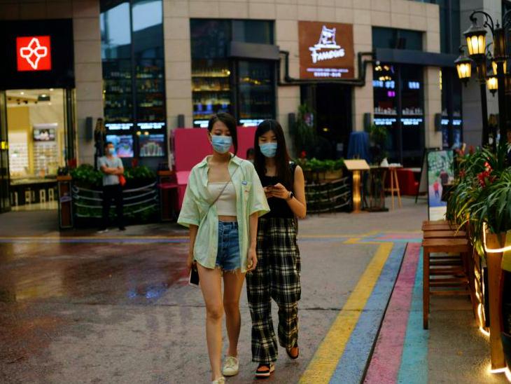 गुरुवार रात बीजिंग के एक बाजार से गुजरती महिलाएं। यहां संक्रमण की दूसरी लहर सामने आई है। तीन बड़े होलसेल मार्केट बंद कर दिए गए हैं। अमेरिका ने चीन पर बीजिंग के आंकड़े छिपाने के आरोप लगाए हैं।