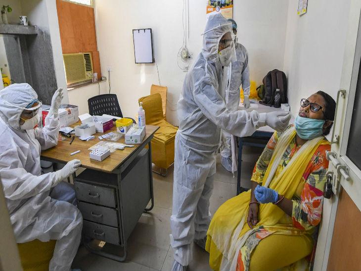 दिल्ली के एक सरकारी अस्पताल में गुरुवार को एक महिला का स्वैब सैंपल लेते स्वास्थ्यकर्मी। गृह मंत्रालय के निर्देश के बाद दिल्ली में सैंपल टेस्टिंग में तेजी आई है। - Dainik Bhaskar