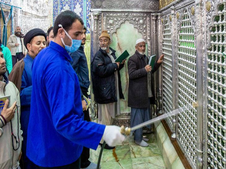 ईरान के कोम स्थित फातेमा मस्जिद को सैनिटाइज करता एक कर्मचारी।