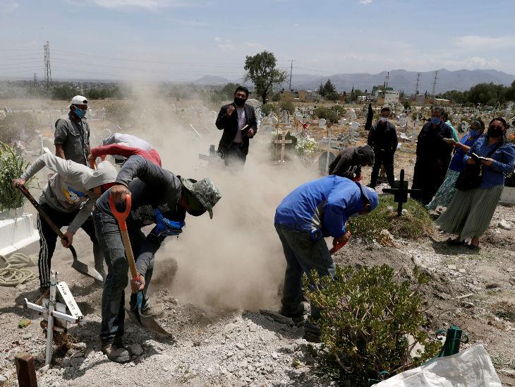 मैक्सिको सिटी के पास सैन इफ्रेन में कोरोना से जान गंवाने वाले व्यक्ति को दफनाने के लिए कब्र खोदने में जुटे कब्रिस्तान के कर्मचारी।