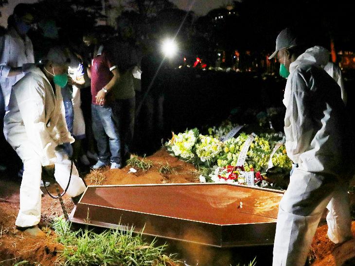 ब्राजील के साओ पाउलो स्थित कब्रिस्तान में एक कोरोना संक्रमित का शव दफनाते कर्मचारी।