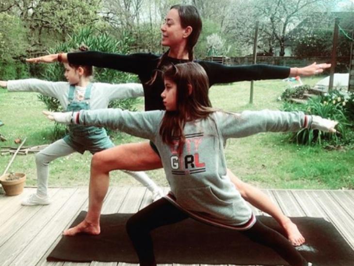 पैरिस की योगा टीचर डाफने ओलिवुड अपनी भतीजियों अवा और ताली के साथ लॉकडाउन में योग करते हुए