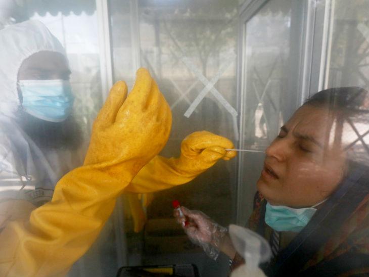 पाकिस्तान के कराची शहर में एक महिला का कोरोना सैंपल लेता स्वास्थ्यकर्मी। देश में संक्रमण से अब तक 81 हजार से ज्यादा लोग ठीक हो चुके हैं।