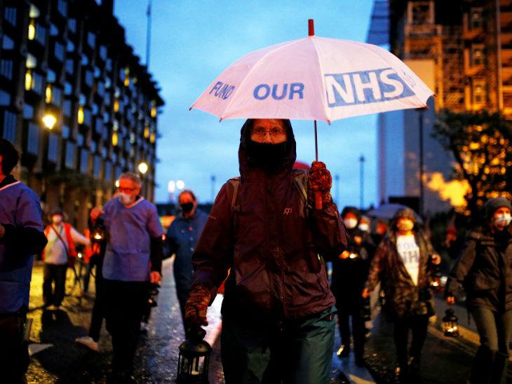 ब्रिटेन में सरकार के खिलाफ प्रदर्शन करते एनएचएस स्टाफ के लोग। सरकार पर महामारी से ठीक से नहीं निपटने का आरोप है।