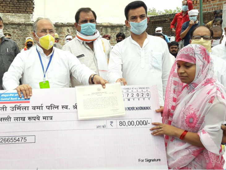 यह तस्वीर झांसी की है। यहां भोजला गांव के रहने वाले सिपाही सुल्तान सिंह कानपुर मुठभेड़ में बदमाशों की गोली का शिकार हुए थे। मंगलवार को प्रभारी मंत्री राम नरेश ने मृतक सिपाही की पत्नी को सरकार की तरफ से आर्थिक सहायता दी। - Dainik Bhaskar