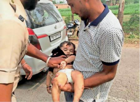 मासूम को उठाकर अस्पताल ले जाते लोग और पुलिस। - Dainik Bhaskar