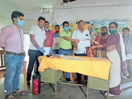 कर्मी को सम्मानित करते सवास्थ्य प्रबंधक व अन्य। - Dainik Bhaskar