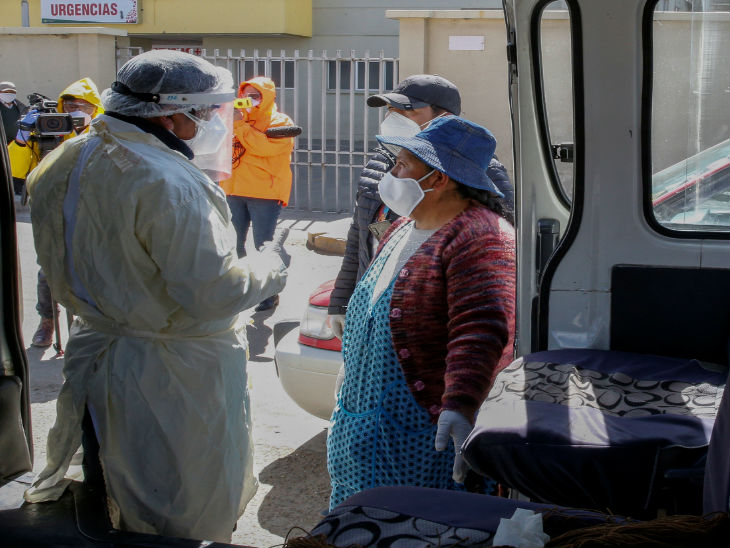 बोलिविया के ला पाज में रविवार को संदिग्ध संक्रमितों से पूछताछ करता एक स्वास्थ्यकर्मी।