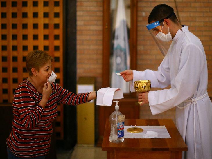 मैक्सिको की राजधानी न्यू मैक्सिको सिटी में रविवार को चर्च के कार्यक्रम में एक महिला को वेफर्स देते एक पादरी।