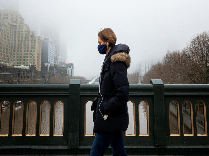 ऑस्ट्रेलिया के मेलबर्न शहर स्थित प्रिंस ब्रिज से गुजरता मास्क पहना एक व्यक्ति। यहां सिर्फ जरूरी काम के लिए बाहर निकलने की इजाजत दी गई है।