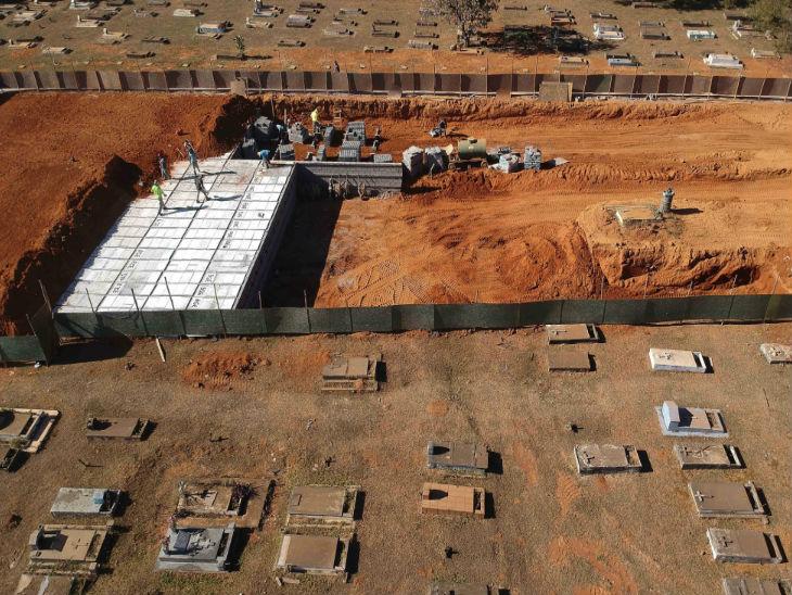 ब्राजील की राजधानी ब्रासीलिया में शुक्रवार को एक कब्रिस्तान में नए शवों को दफनाने के लिए जगह बनाते कर्मचारी।