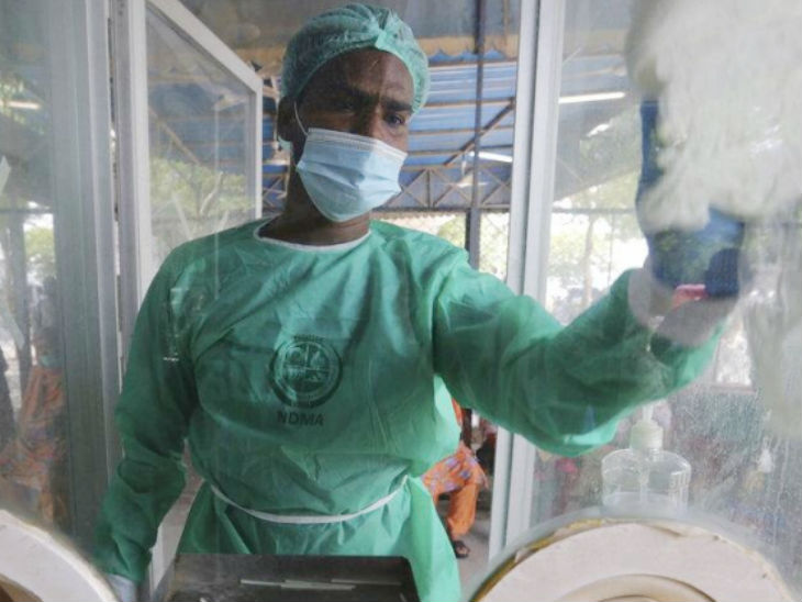 पाकिस्तान के कराची शहर में शुक्रवार को एक टेस्टिंग सेंटर पर लगे कांच की सफाई करता एक कर्मचारी।