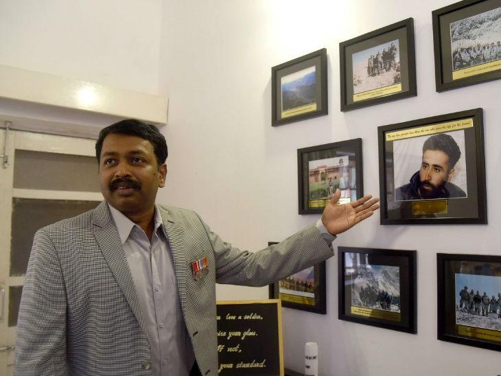 तस्वीर में कैप्टन नागप्पा अपने सीनियर कैप्टन विक्रम बत्रा की फोटो दिखाते हुए। दोनों साथ में करिगल की लड़ाई लड़े थे।