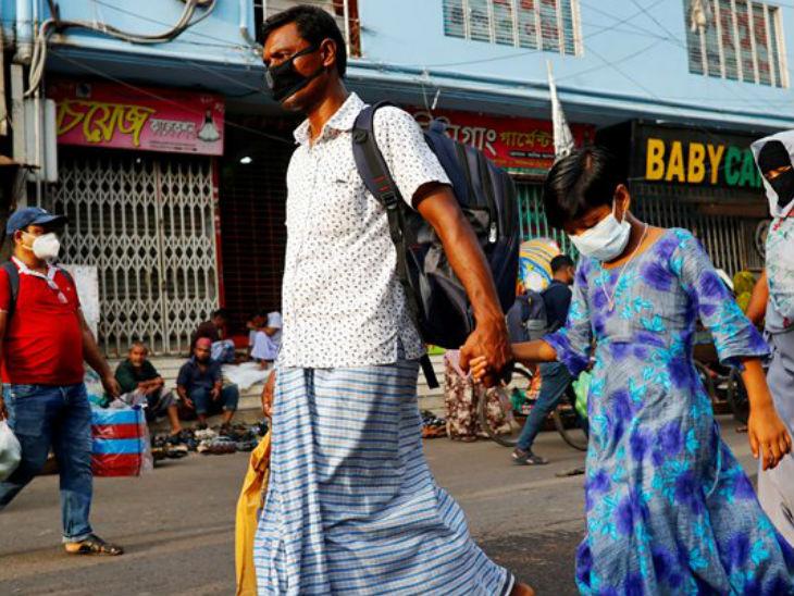 बांग्लादेश की राजधानी ढाका की एक सड़क पर मास्क लगाकर जाते लोग। यहां अब तक 2 हजार से ज्यादा लोगों की मौत हुई है।
