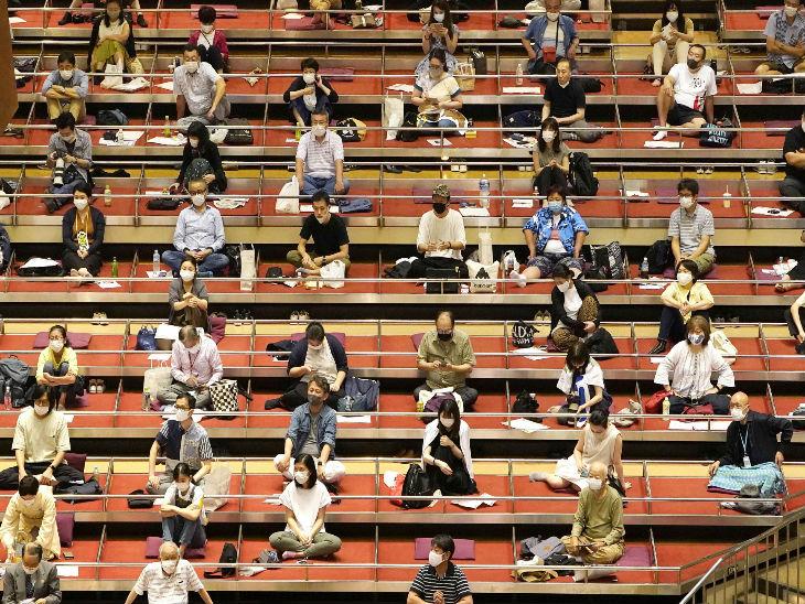 जपान के टोक्यो में रविवार को मास्क लगाकर और सोशल डिस्टेंसिंग का पालन करते हुए सूमो टूर्नामेंट देखते लोग।