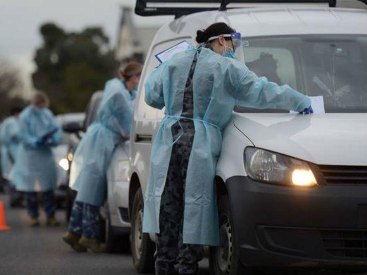 ऑस्ट्रेलिया के विक्टरिया राज्य की सीमा से गाड़ियों से आने वाले लोगों की जांच करते ऑस्ट्रेलिया डिफेंस फोर्स के जवान।