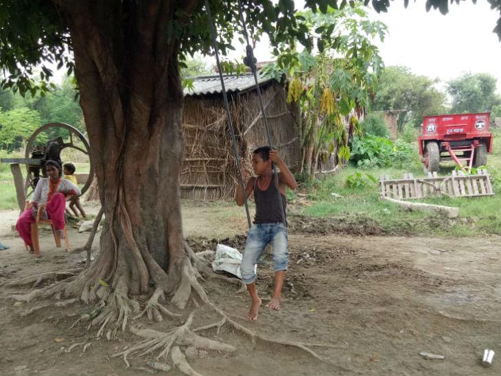 तस्वीर नेऊर के पुरवा गांव की है, जहां बच्चा अपने घर के आगे लगे पेड़ पर झूला झूल रहा है।