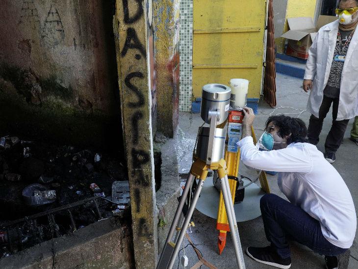 रियो डि जनेरियो के सैंटा मार्टा स्लम एरिया में इक्विपमेंट लगाते वैज्ञानिक। यह इक्विपमेंट ड्रॉप लेट्स के जरिए हवा में फैलने वाले वायरस को कलेक्ट करेगा।