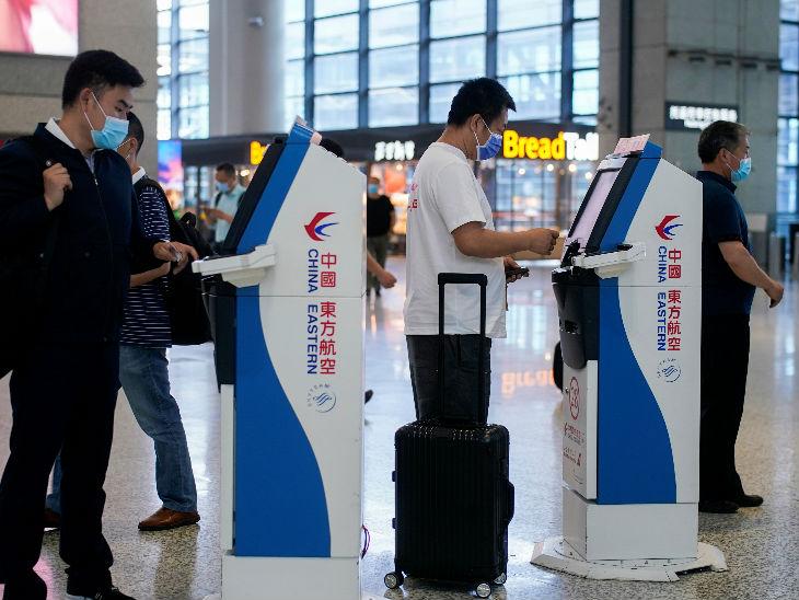 चीन में शंघाई में एक एयरपोर्ट पर यात्री मास्क लगाए नजर आए। चीन में संक्रमण की दूसरी लहर का खतरा मंडरा रहा है।