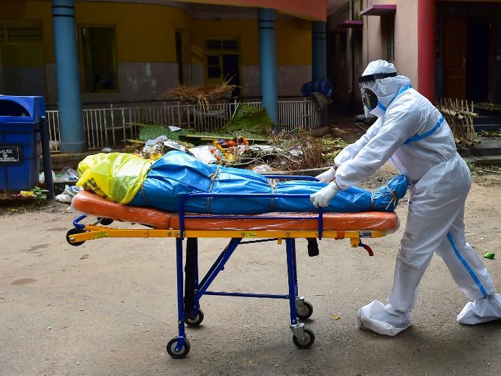 फोटो बेंगलुरु की है। संक्रमित मरीज की मौत के बाद उसके शव को अंतिम संस्कार के लिए ले जाता स्वास्थ्यकर्मी। बेंगलुरु में अब तक 917 लोग संक्रमण की चपेट में आकर जान गंवा चुके हैं। - Dainik Bhaskar
