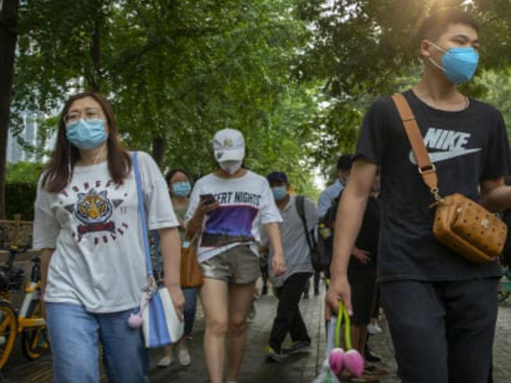 चीन की राजधानी बीजिंग की एक सड़क से शुक्रवार को मास्क लगाकर गुजरते कुछ लोग।