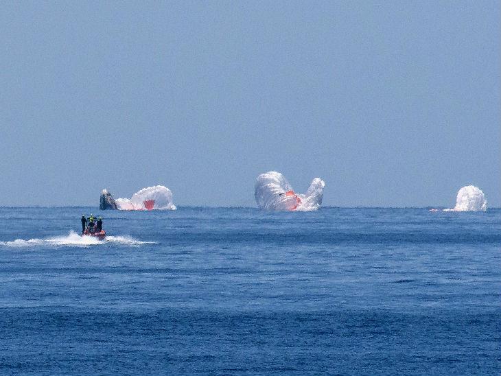 लैंडिंग के तुरंत बाद किनारे पर इंतजार कर रही नासा की टीम बोट के जरिए ड्रैगन कैप्सूल तक पहुंची। लैडिंग में इस्तेमाल किए गए पैराशूट समुद्री सतह पर तैरते नजर आ रहे हैं।