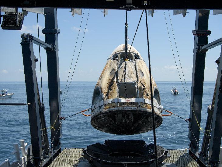समुद्री सतह पर तैरते स्पेसएक्स ड्रैगन को क्रेन की मदद से बाहर निकाल कर एक बड़ी बोट पर रखा गया।