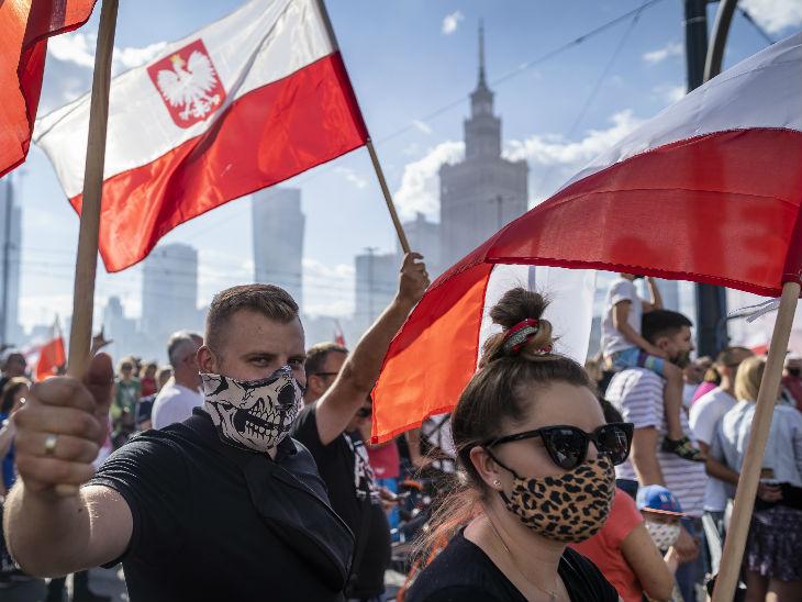 पोलैंड की राजधानी वरसॉ में शनिवार को दूसरे वर्ल्ड वार में नाजियों से मिली जीत की याद में होने वाले कार्यक्रम में लोग मास्क पहनकर शामिल हुए।