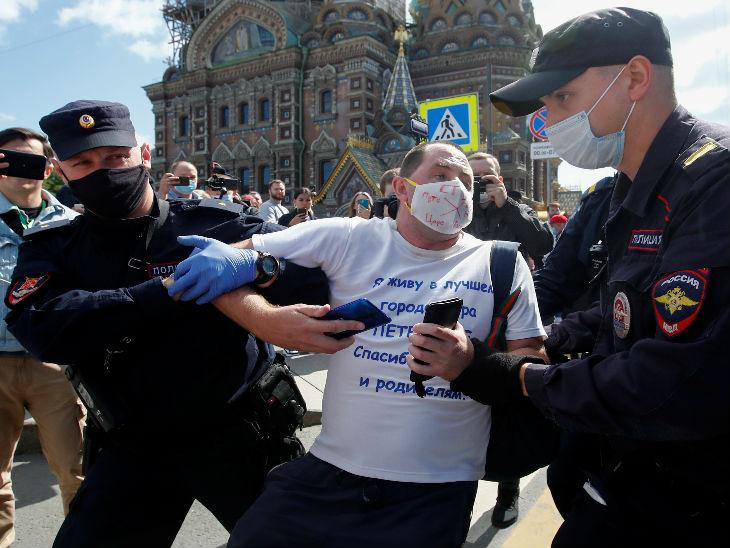 रूस के सेंट पीटर्सबर्ग में शनिवार को एंटी क्रेमलिन प्रदर्शन में शामिल एक व्यक्ति को गिरफ्तार करते सुरक्षाकर्मी। यहां पुलिस ने प्रदर्शनकारियों पर महामारी से जुड़े नियम तोड़ने का आरोप लगाया है।