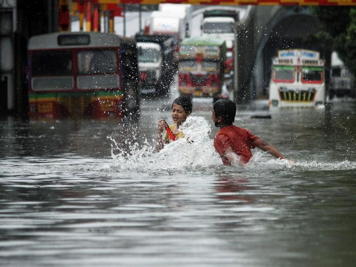 मुंबई की सड़कें अब किसी तालाब की तरह नजर आ रही हैं। ऐसी ही एक सड़क पर खेलते हुए बच्चे।