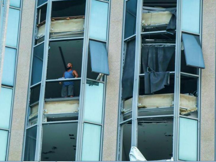 जिस शिपमेंट में धमाका हुआ, उससे कुछ दूरी पर एक इमारत से यह व्यक्ति हादसे वाली जगह को देख रहा है। इस इमारत के सभी शीशे और खिड़कियां टूट चुकी हैं।