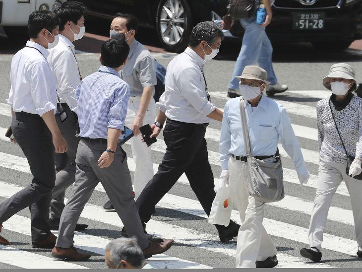 जापान की राजधानी टोक्यो की एक व्यस्त सड़क से मास्क लगाकर जाते लोग। टोक्यो में सबसे ज्यादा संक्रमण के मामले सामने आए हैं।