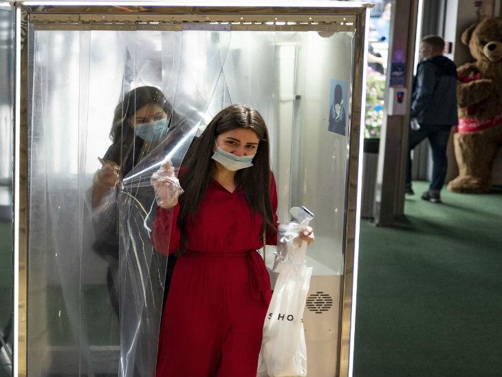 रूस की राजधानी मॉस्को के एक शॉपिंग सेंटर में डिसइन्फेक्ट करने के लिए बनाए गए टनल से बाहर निकलती एक महिला।