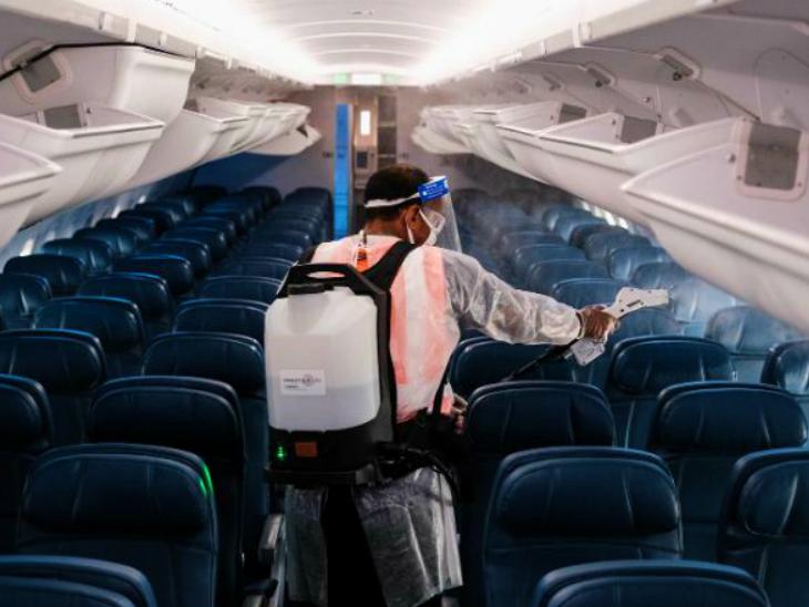 अमेरिका में एर्लिंग्टन के रोनाल्ड रीगन नेशनल एयरपोर्ट पर 22 जुलाई को एयरक्राफ्ट को सैनिटाइज करता कर्मचारी।