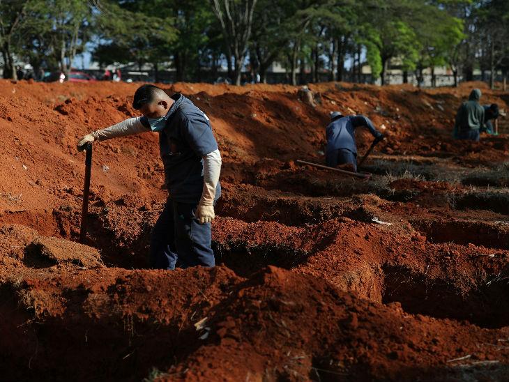 ब्राजील के साओ पाउलो राज्य स्थित एक कब्रिस्तान में शनिवार को कब्र तैयार करने में जुटे कर्मचारी। यह अमेरिका के बाद दुनिया का सबसे प्रभावित देश है।