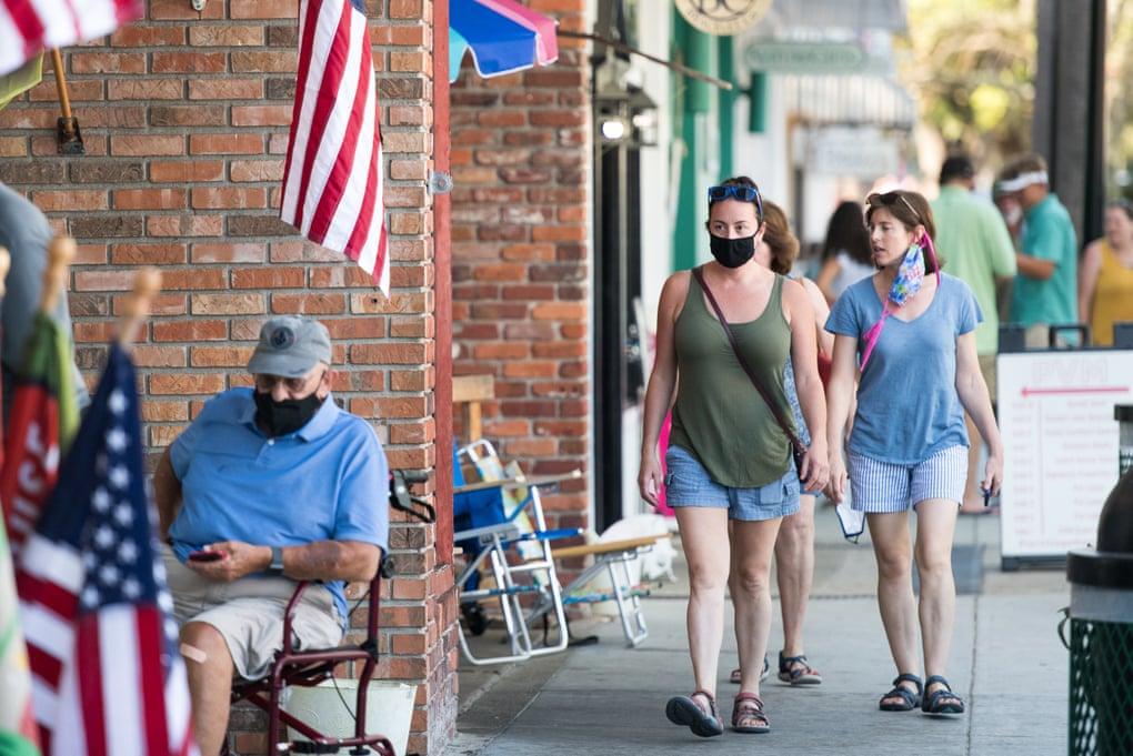 अमेरिका के जॉर्जिया की एक सड़क से गुजरते लोग। अब भी यहां कई लोग मास्क लगाने में लापरवाही करते नजर आ रहे हैं।