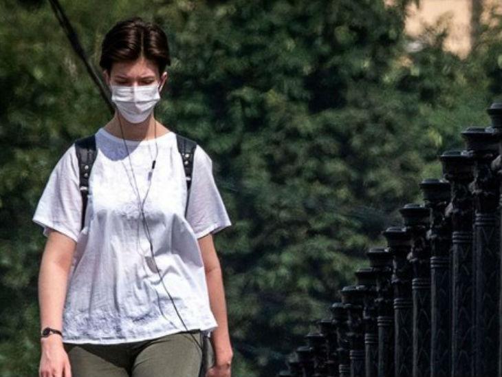 रूस की राजधानी मॉस्को में सेंट्रल ब्रिज पर मास्क लगाकर गुजरती एक महिला। देश में अब तक 14 हजार से ज्यादा लोगों की मौत हुई है।