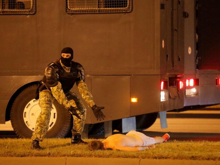 प्रदर्शन के दौरान घायल हुए एक व्यक्ति को उठाने के लिए मदद मांगता सुरक्षाकर्मी।